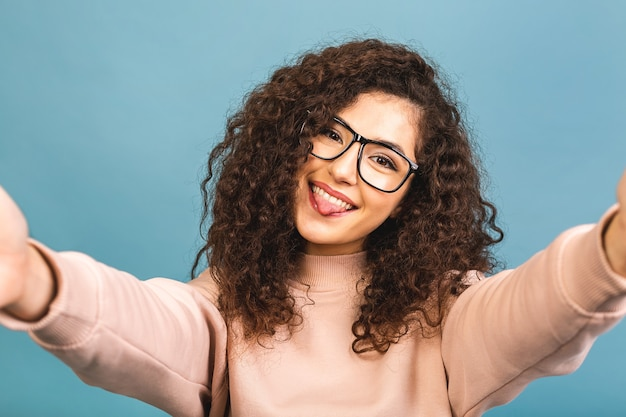 Время селфи. молодая веселая привлекательная курчавая брюнетка улыбается изолированной на синем фоне. она делает селфи на камеру своего телефона.