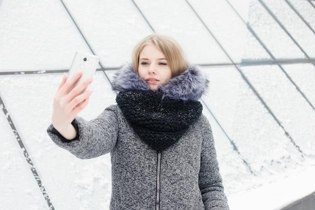셀카 타임, 젊은 펑키 블로거가 소셜 네트워크 페이지의 사진을 만들고 있습니다. selfie를 복용하는 젊은 행복 한 여자. 춥고 화창한 날씨. 여자 겨울 개념입니다.