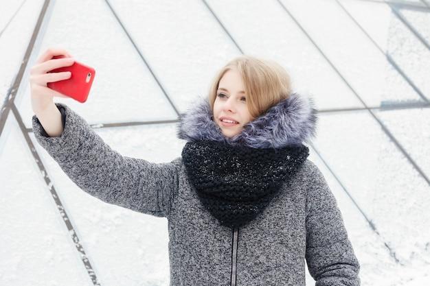 셀카 시간, 젊은 펑키 블로거가 소셜 네트워크 페이지에서 사진을 만들고 있습니다. selfie를 복용 하는 젊은 행복 한 여자. 추운 화창한 날씨입니다. 여자 겨울 개념입니다.