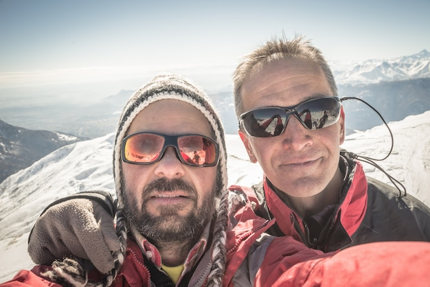 Selfie of two alpinists on the mountain top in winter