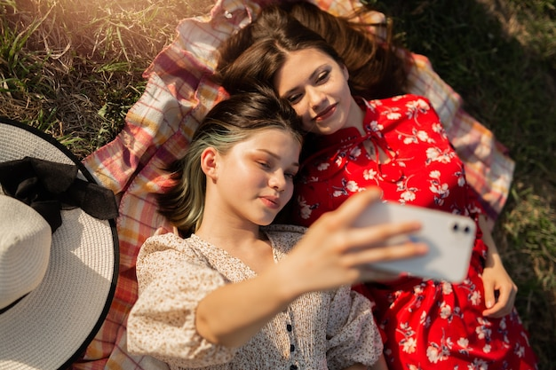 Selfie of two beautiful young woman on a summer picnic