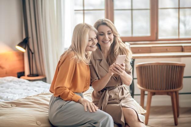 셀카. 두 명의 웃는 금발 여성이 침대에 앉아 스마트폰으로 셀카를 찍고 있다