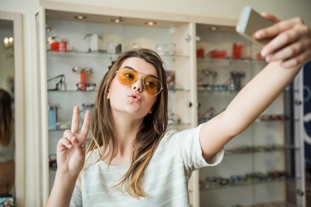 メガネ店でスタイリッシュなフェミニンな若い女子学生がグラマラスな顔を作り、流行のサングラスの新しいペアでselfieを取りながらvサインを表示