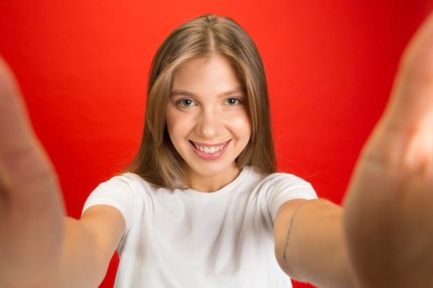 自分撮りビュー。コピースペースと赤い壁に若い白人女性の肖像画。金髪の女性モデル。