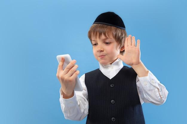 セルフィー、vlog。青い壁に隔離された若い正統派ユダヤ人の少年の肖像画。プリム、ビジネス、お祭り、休日、子供時代、お祝いのペサッハまたは過越の祭り、ユダヤ教、宗教の概念。