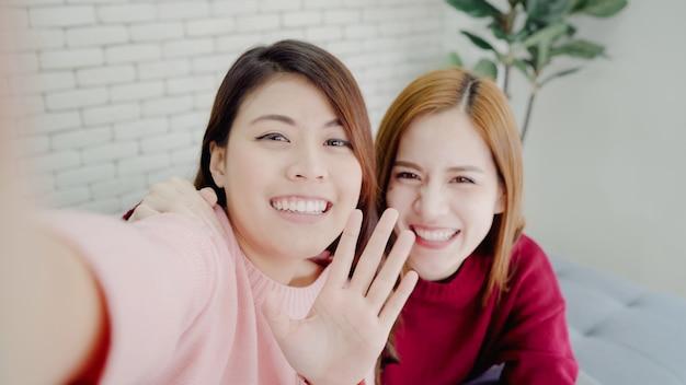 アジアのブロガーの女性がスマートフォンselfieを使用して自宅の居間でvlogビデオを録画する