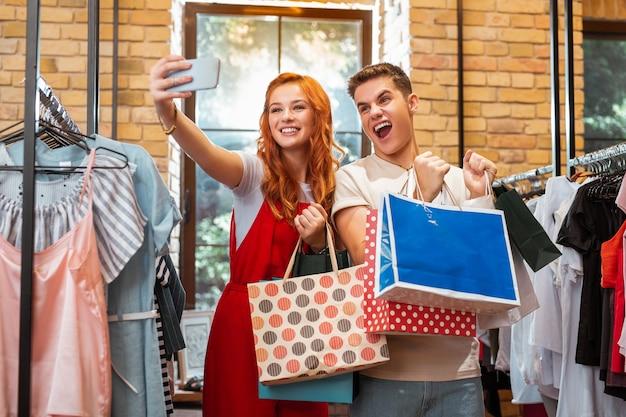 Селфи во время покупок. эмоциональная молодая пара посещает магазин модной одежды и улыбается, делая селфи со своими покупками