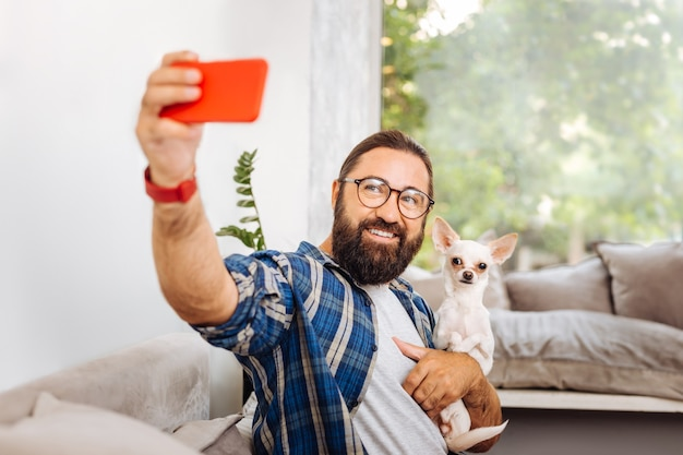 Selfie with dog. smiling bearded man sitting on light grey sofa making selfie with little cute dog