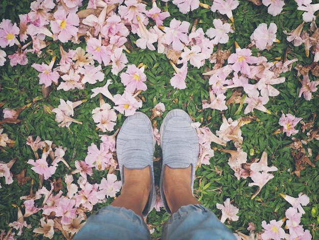 Selfie woman feet on pink trumpet flowers dropped over green grass.