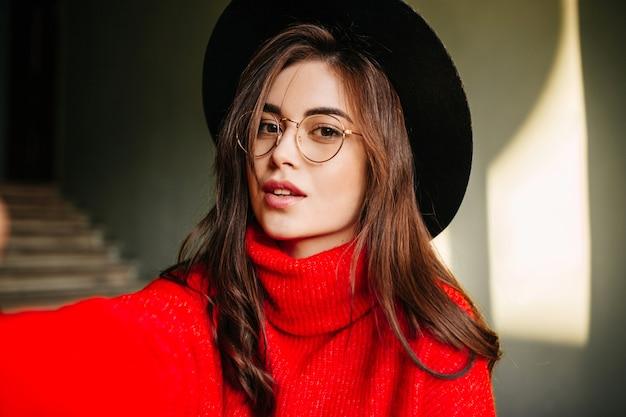 Selfie di giovane ragazza europea con capelli scuri ondulati in maglione rosso. modello in cappello e occhiali in posa