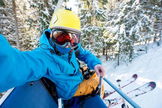 空、黄色いヘルメット、スキーマスクを身に着けている完全装備のスキーヤーが山でスキーリフトに乗っている間、selfieを撮るショット