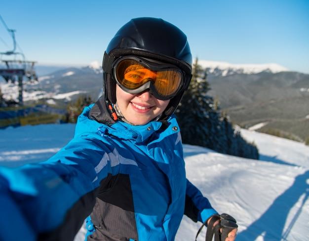 晴れた冬の美しい日にスキーリゾートの山でスキーをした後、斜面で休んでいる間、selfieを取って、笑顔の幸せな女性スキーヤーのクローズアップの肖像画