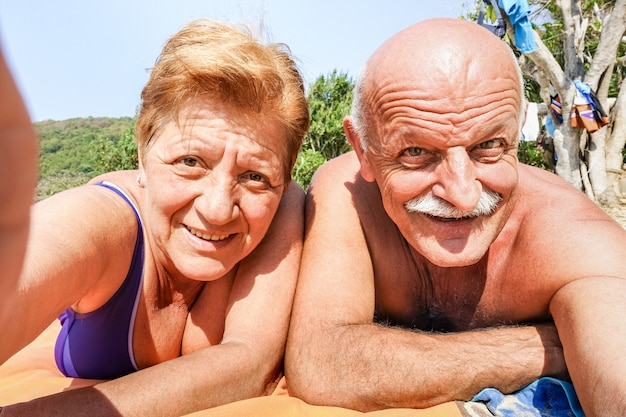 熱帯のツアーでタイ旅行のビーチリゾートでselfieを取ってシニアの幸せなカップル