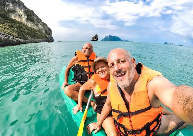幸せな先輩母と父と息子のタイでカヤックの遠足でselfieを取る