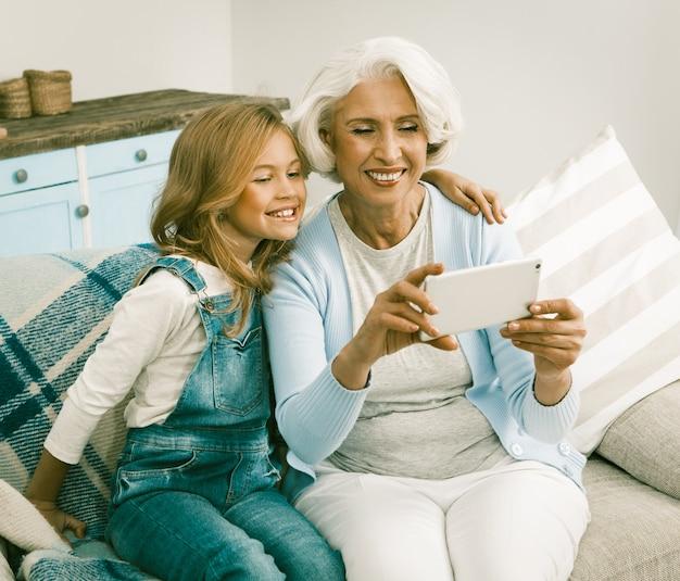 おばあちゃんと彼女の陽気な孫娘がselfieを作る
