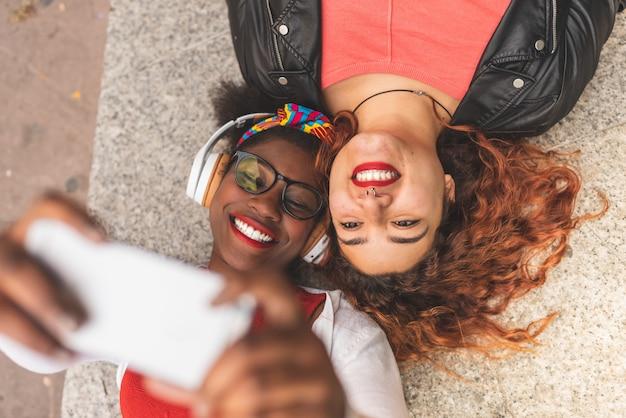 Две подростковые подруги, принимая selfie на открытом воздухе.