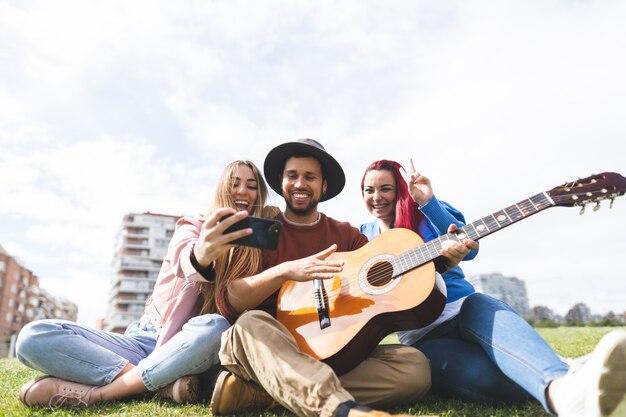 屋外でギターを弾き、selfieを取っている友人のグループ