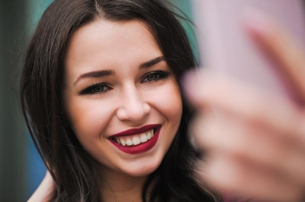 若い女の子は、夏の街に電話で手からselfieを取る