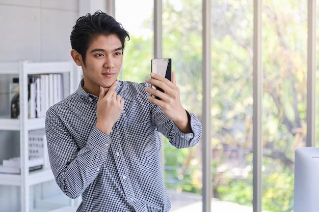 Портрет умного молодого азиатского бизнесмена используя умный мобильный телефон для того чтобы сфотографировать selfie в комнате офиса.