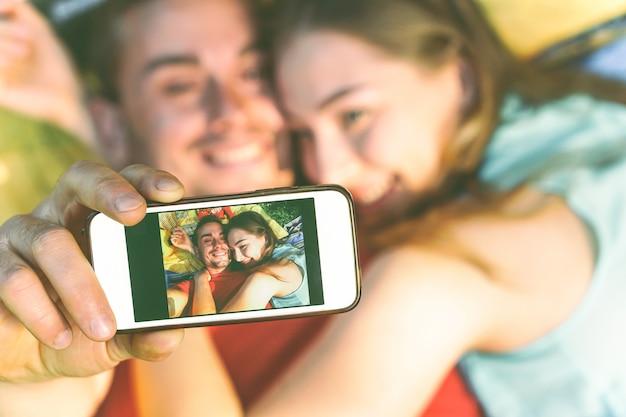 携帯電話でselfieを取って草の上に横たわって取っている恋人たちの若いカップル