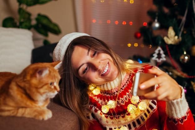 Празднование рождества с кошкой. женщина берет selfie с питомцем в шапке санта-клауса на новогодней елке у себя дома.