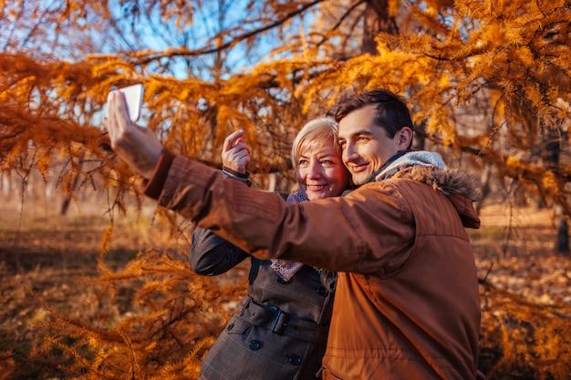 秋の公園でスマートフォンを使用して母親と一緒にselfieを取って大人の息子。家族の時間
