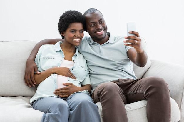 妊娠中のカップルが自宅で携帯電話でselfieを取る