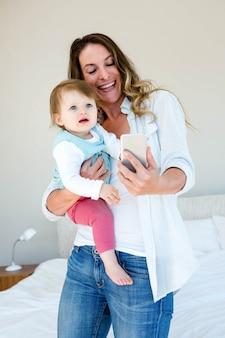 彼女の携帯電話で赤ちゃんとselfieを取って笑顔の女性