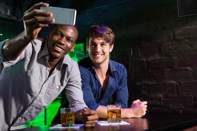 二人の男がバーのカウンターで電話でselfieを取る
