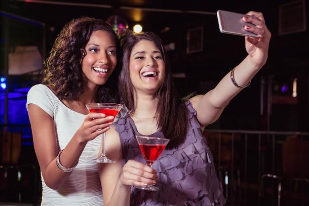 カクテルを飲みながらselfieを取っている若い女性のバー
