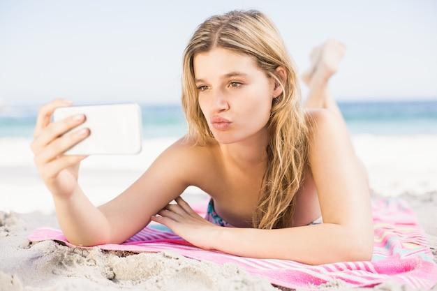 携帯電話でselfieを取る若い女性