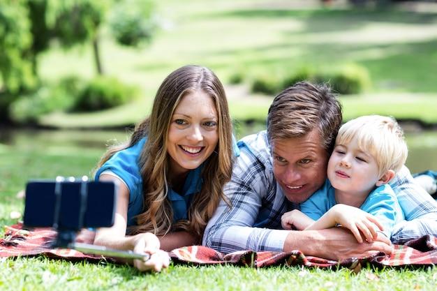 両親と息子が携帯電話でselfieを取る