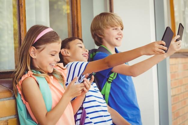 学校の子供たちがselfieを取り、廊下で携帯電話を使用して