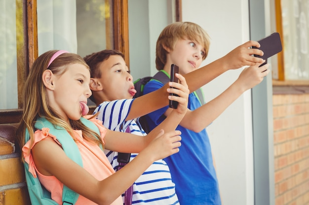 廊下で携帯電話でselfieを取って学校の子供たち