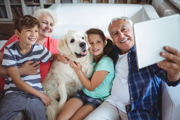 祖父母と孫がデジタルタブレットでselfieを取る