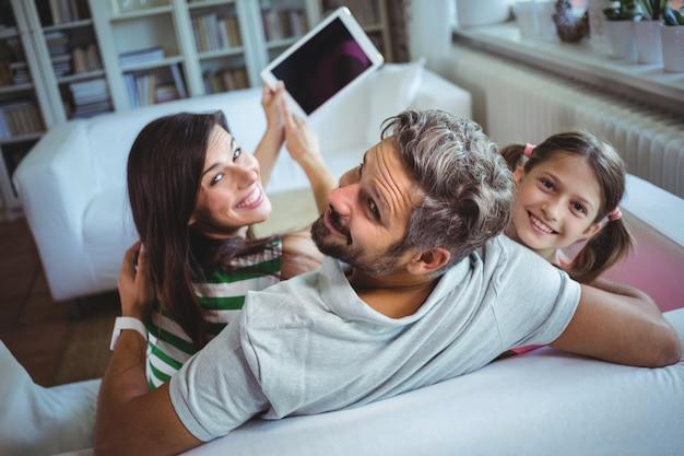 娘とソファの上に座って、デジタルタブレットでselfieをクリックする親