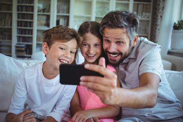 彼の子供とソファに座って、リビングルームでselfieをクリックする父