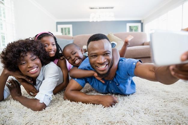 リビングルームで携帯電話からselfieを取って幸せな家族