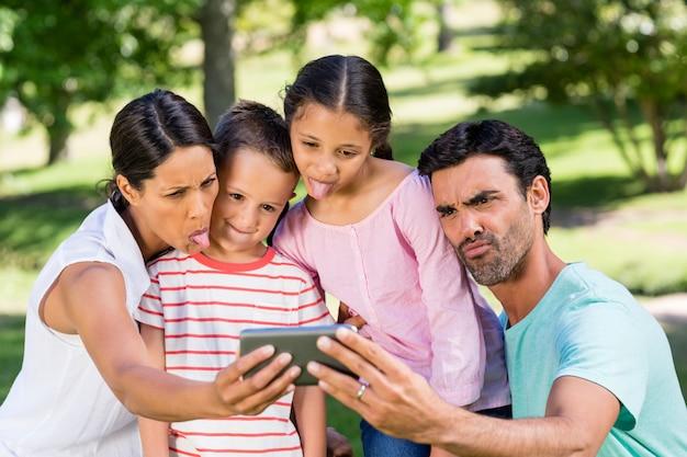 公園で携帯電話からselfieを取って幸せな家族