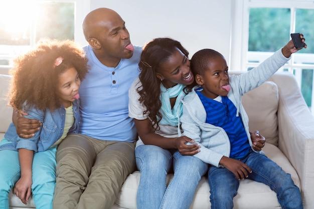 家族が携帯電話からselfieを取る