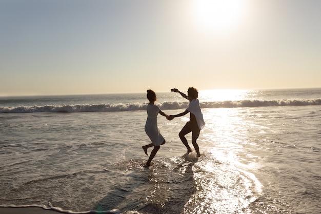 ビーチで携帯電話でselfieをしながら楽しみを持っているカップル