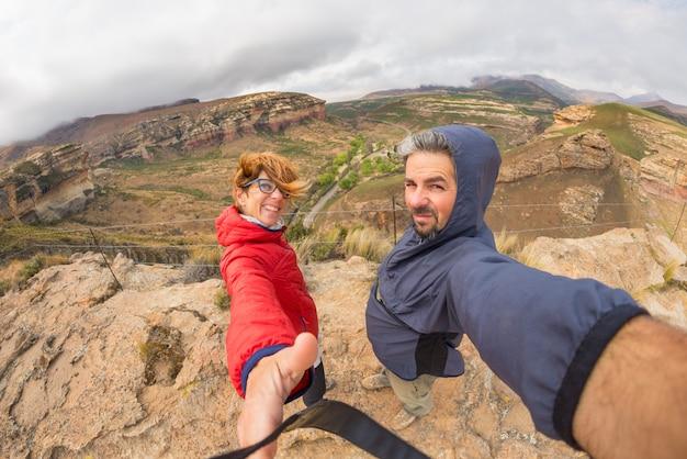 南アフリカの雄大なゴールデンゲートハイランズ国立公園の風の強い山の頂上でselfieを取って伸ばした腕を持つカップル。冒険と旅の人々の概念