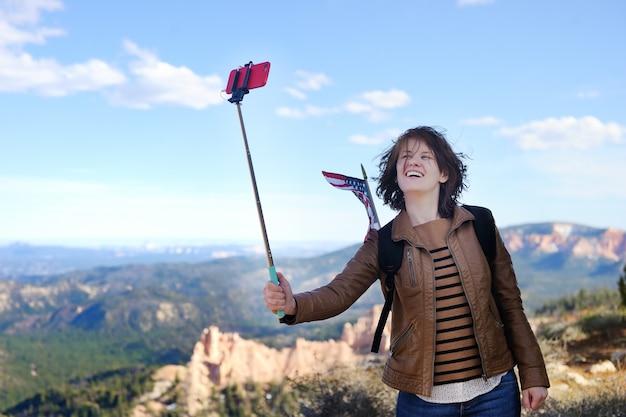 米国ユタ州ブライスキャニオン国立公園でselfie棒で自分の写真を撮る若い女性観光客