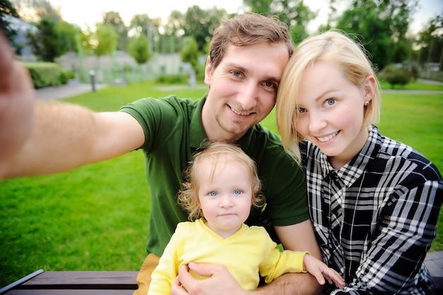 一緒にselfie写真を作る若い美しい幸せな家族