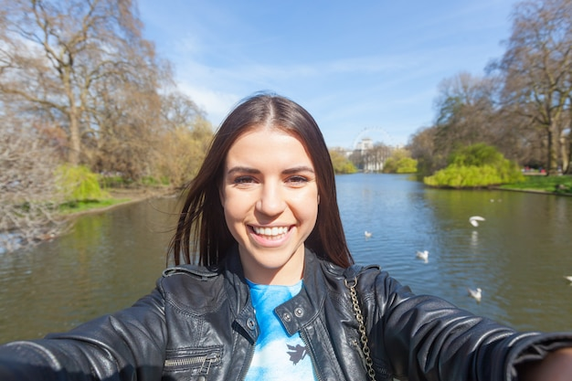 ロンドンの公園で、selfieを取っている若い女性