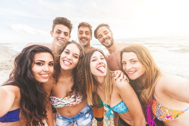 ビーチでselfieを取っている友人の多民族のグループ