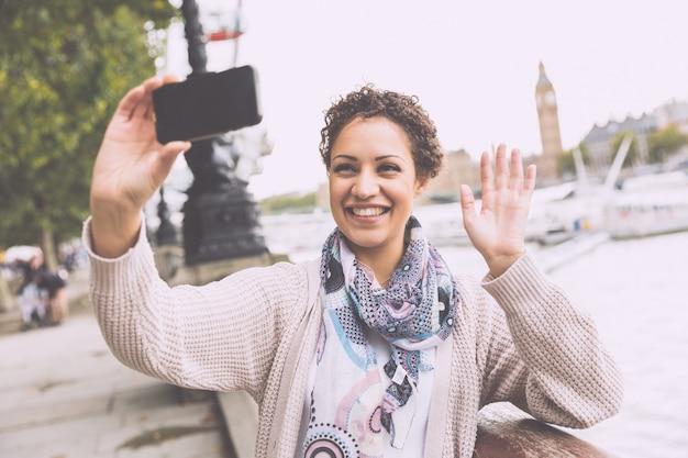 ロンドンでselfieを取って美しい混血女性