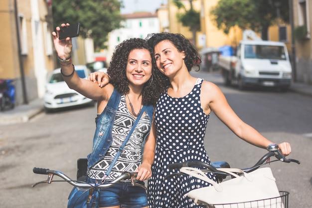 女友達が自転車でselfieを取っています。