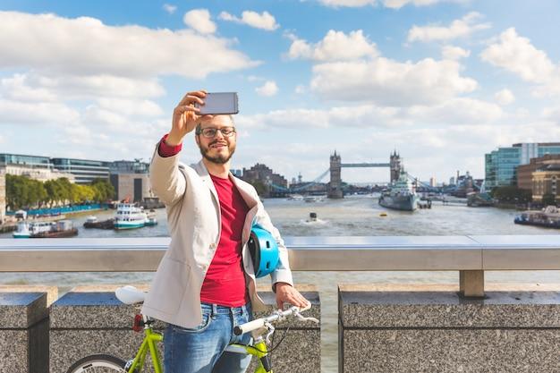 流行に敏感な人が通勤しながらロンドンでselfieを取って