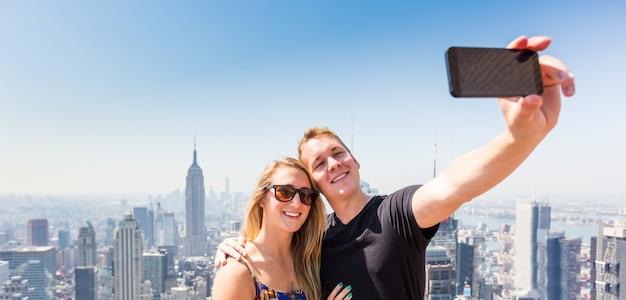 ニューヨークとselfieを取っている若いカップル